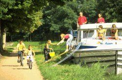 Tarpon 42, boat without license moored at the edge of the canal. The girls are sunbathing on the deck, the children are cycling on the towpath