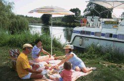Picnic with family next to a boat without a license moored at the bank on the Seille in southern Burgundy
