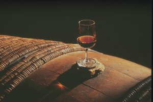 Red pineau des Charentes glass on an oak barrel